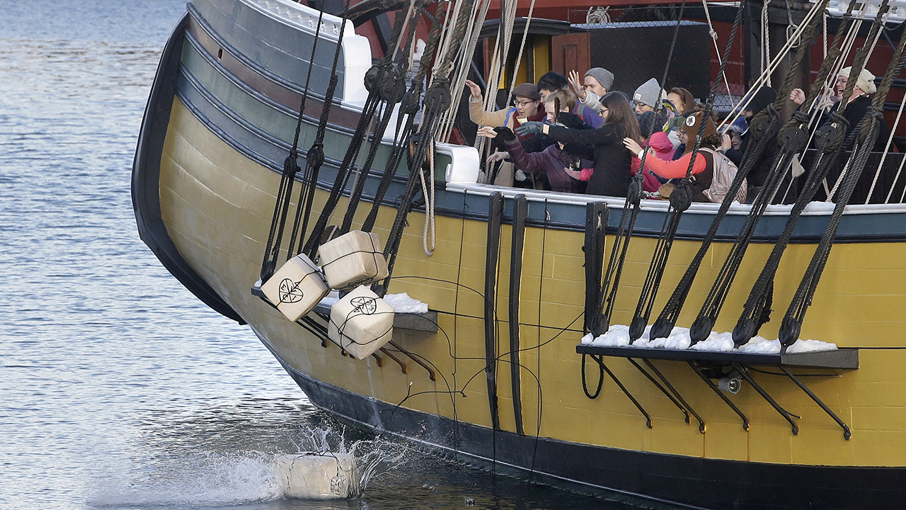 In this Monday, Dec. 11, 2017 photo visitors to the Boston Tea Party Museum throw replicas of historic tea containers into Boston Harbor from aboard a replica of the vessel Beaver.