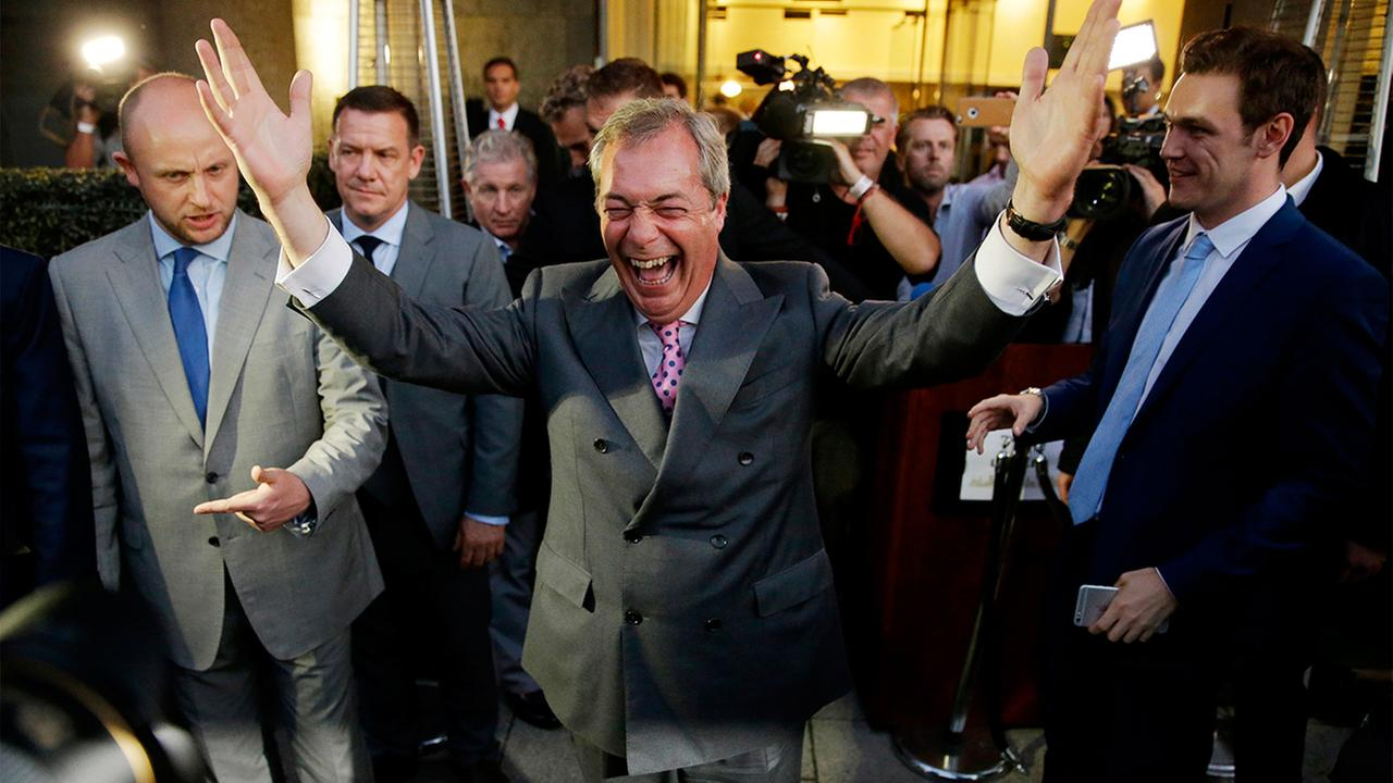 Nigel Farage, the leader of the UK Independence Party celebrates and poses for photographers as he leaves a Leave.EU organization party for the British European Union.