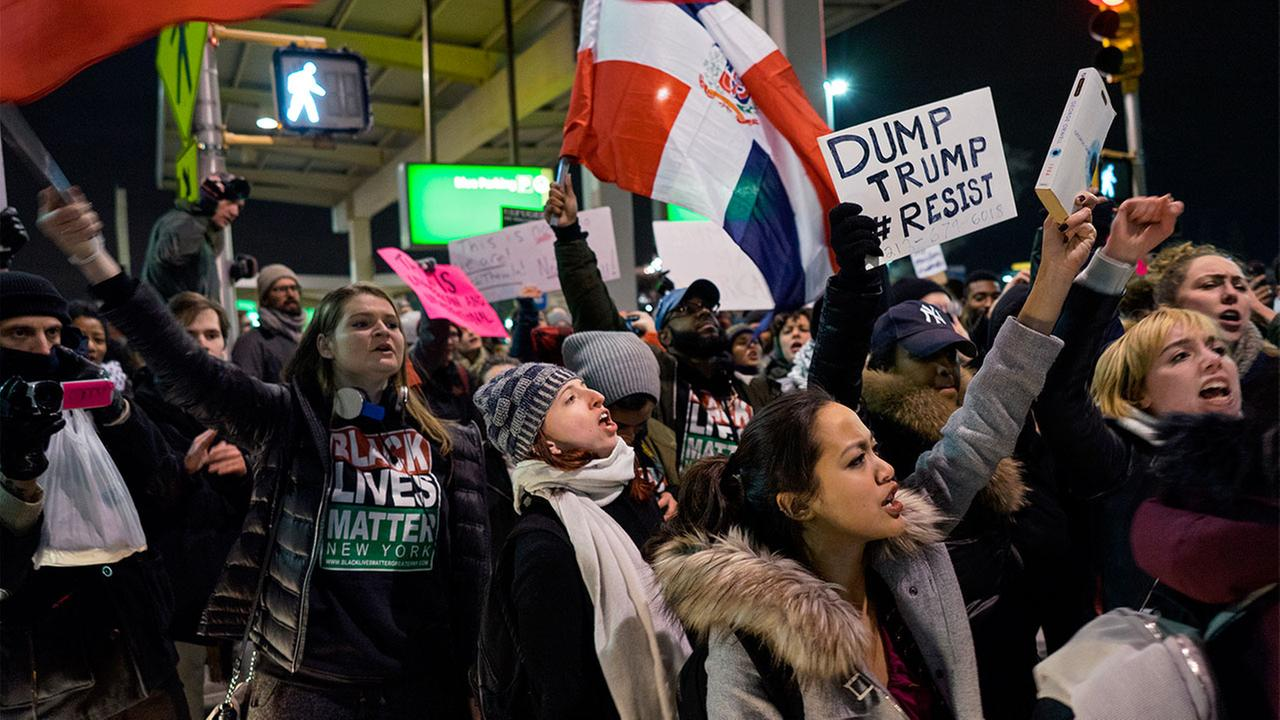 Protesters are surrounded by police officers and travelers as they pass through an exit of Terminal 4 at John F. Kennedy International Airport in New York, Saturday, Jan. 28, 2017.