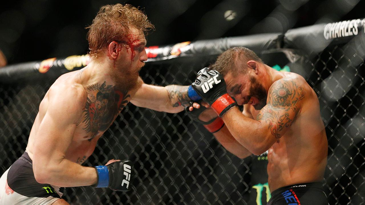 Conor McGregor hits Chad Mendes during their interim featherweight title mixed martial arts bout at UFC 189 on Saturday, July 11, 2015, in Las Vegas.