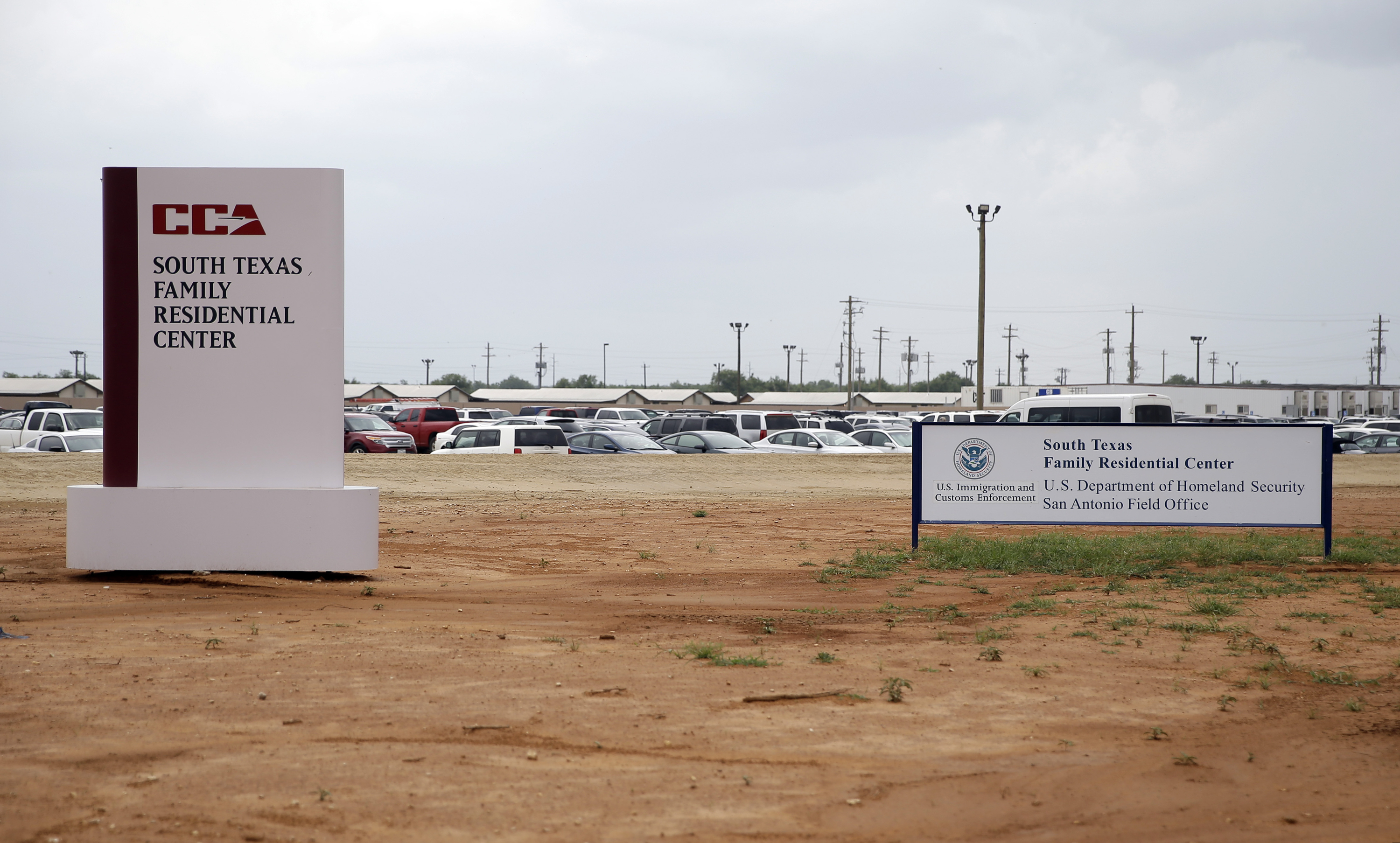 FILE - In this June 30, 2015, file photo, signs are seen at the entrance to the South Texas Family Residential Center in Dilley, Texas.