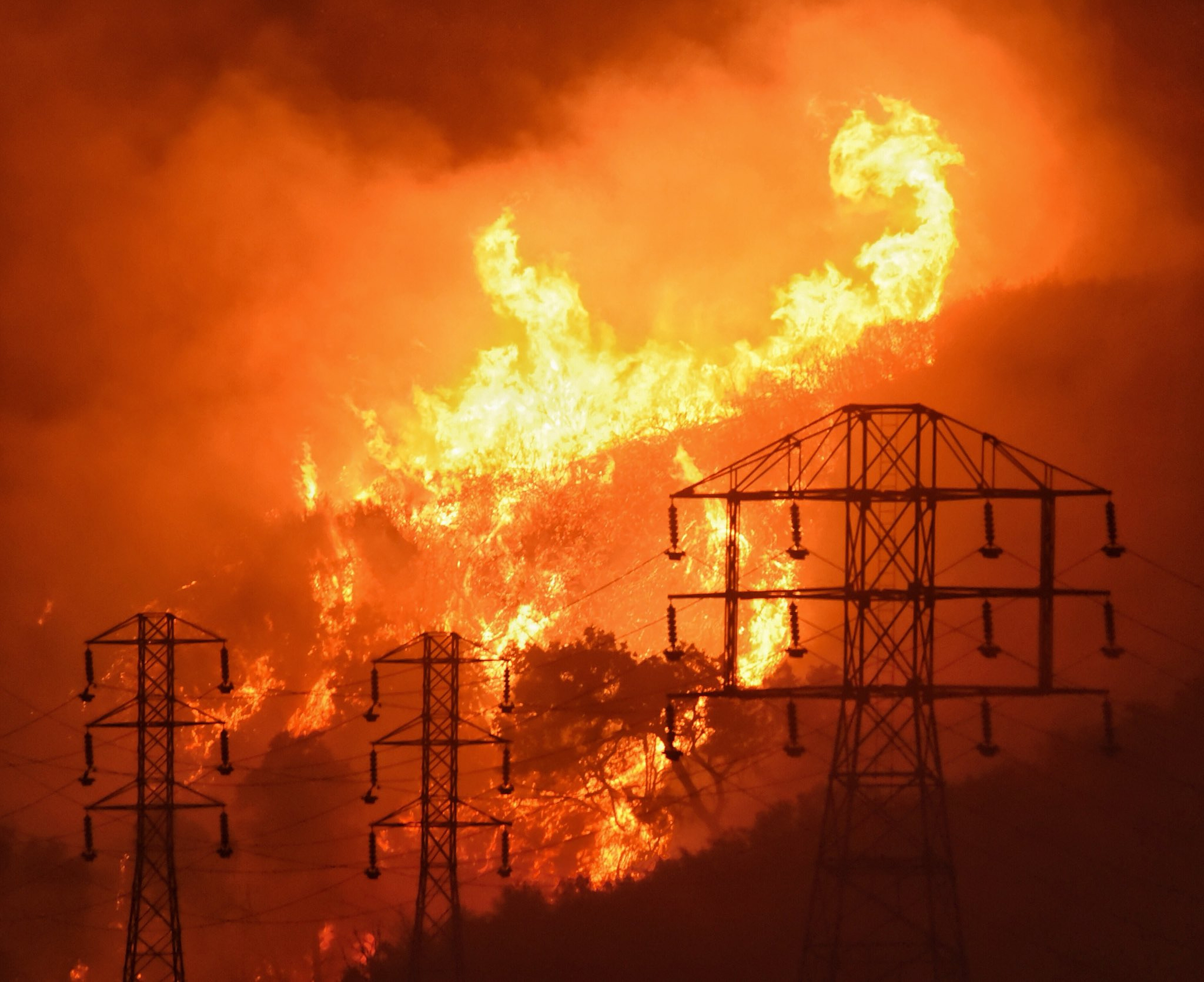 Dec. 16, 2017, file photo provided by the Santa Barbara County Fire Department, flames burn near power lines in Sycamore Canyon near West Mountain Drive in Montecito, Calif.