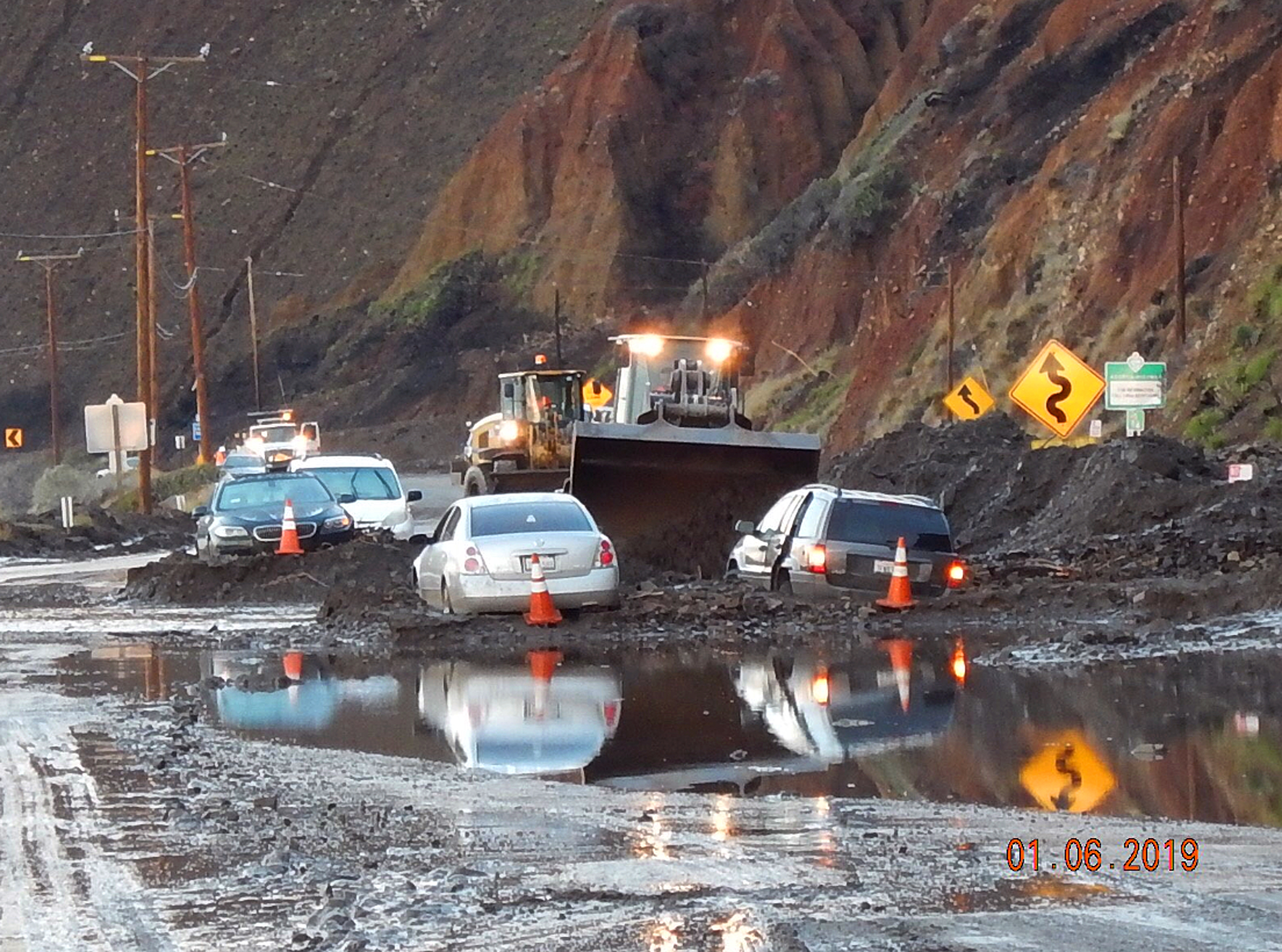 In this Sunday, Jan. 6, 2019 photo, California Department of Transportation (CalTrans) crews work to clear mud and rocks that tumbled onto Pacific Cost Highway in Malibu, Calif.