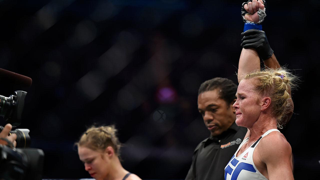 Holly Holm, right, celebrates after defeating Ronda Rousey, left, during their UFC 193 Bantamweight title fight in Melbourne, Australia, Sunday, Nov. 15, 2015.