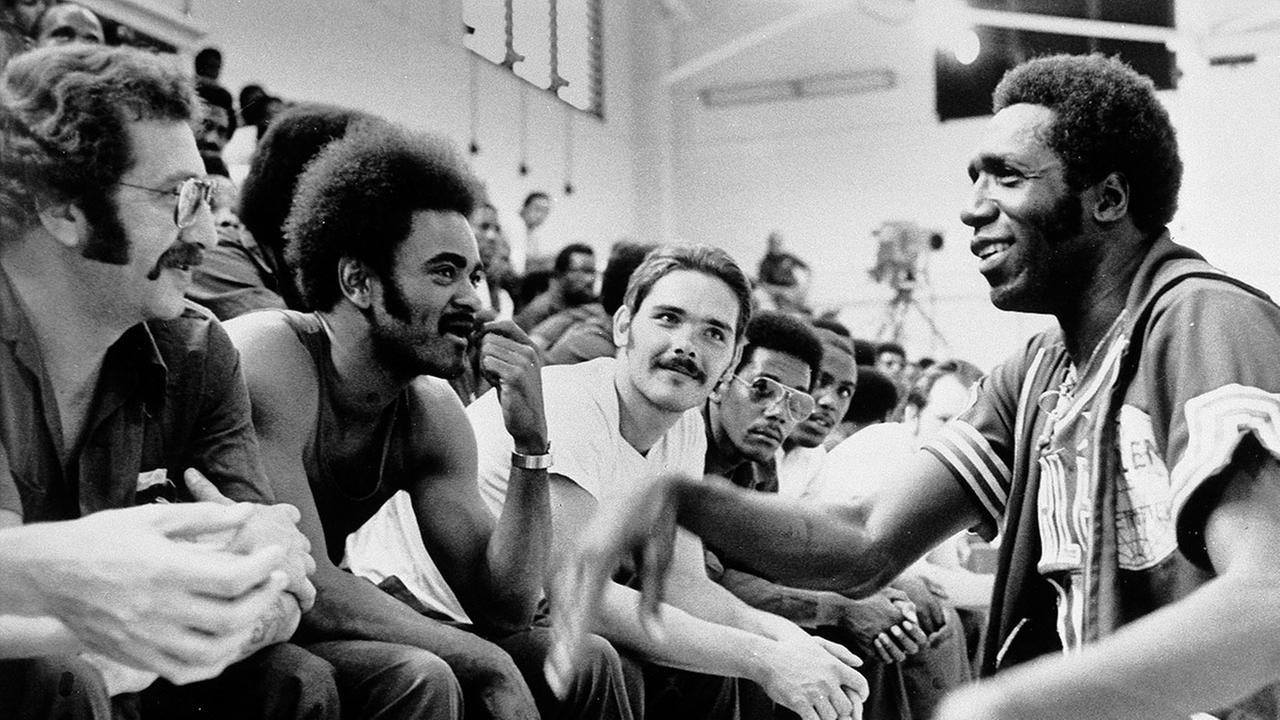 Meadowlark Lemon of the Harlem Globetrotters kneels on the right while talking with Attica Prison inmates, July 2, 1975. (AP Photo)