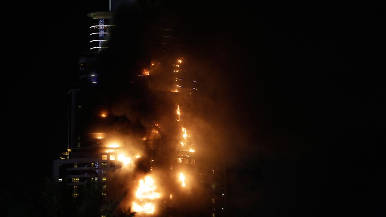 Smoke and flames pouring from a residential building, which also contains the Address Downtown Hotel, in Dubai, United Arab Emirates, Dec. 31, 2015. (AP Photo/Sunday Alamba)