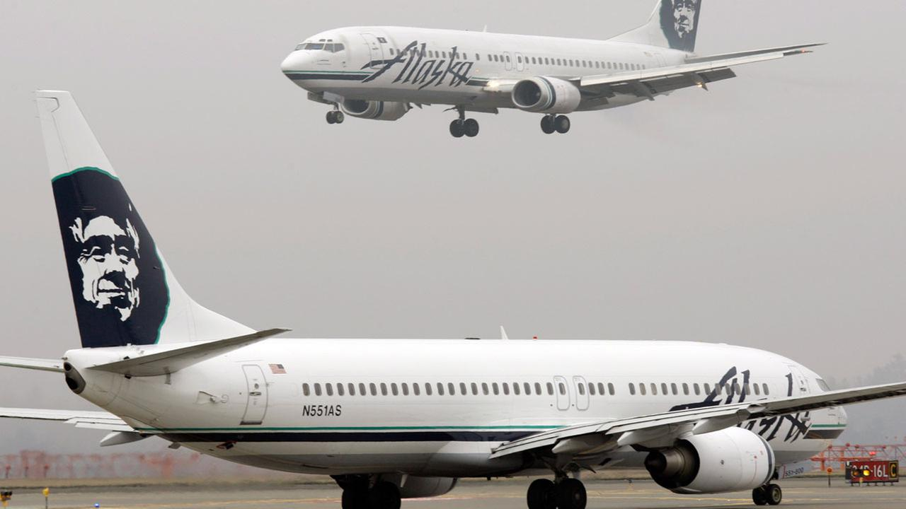 In this 2009 photo, an Alaska Airlines plane comes in for a landing as another taxis for takeoff at Seattle-Tacoma International Airport in Seattle.(AP Photo/Ted S. Warren, File)