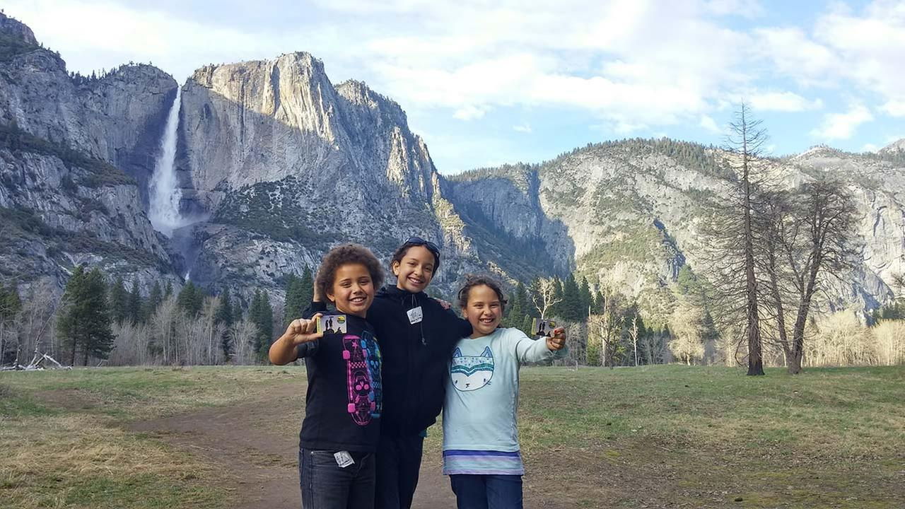 Twin 4th graders, Benson and Kaycee Kirk, show off their Every Kid in a Park pass with their older sister Kaya in front of Yosemite Falls on April 3, 2016.