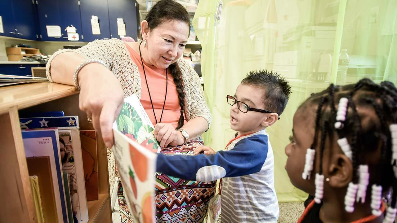 Wishon Elementary School preschool teacher Andrea Wall works with Sonny Molina while Jaeda Worthy waits her turn.