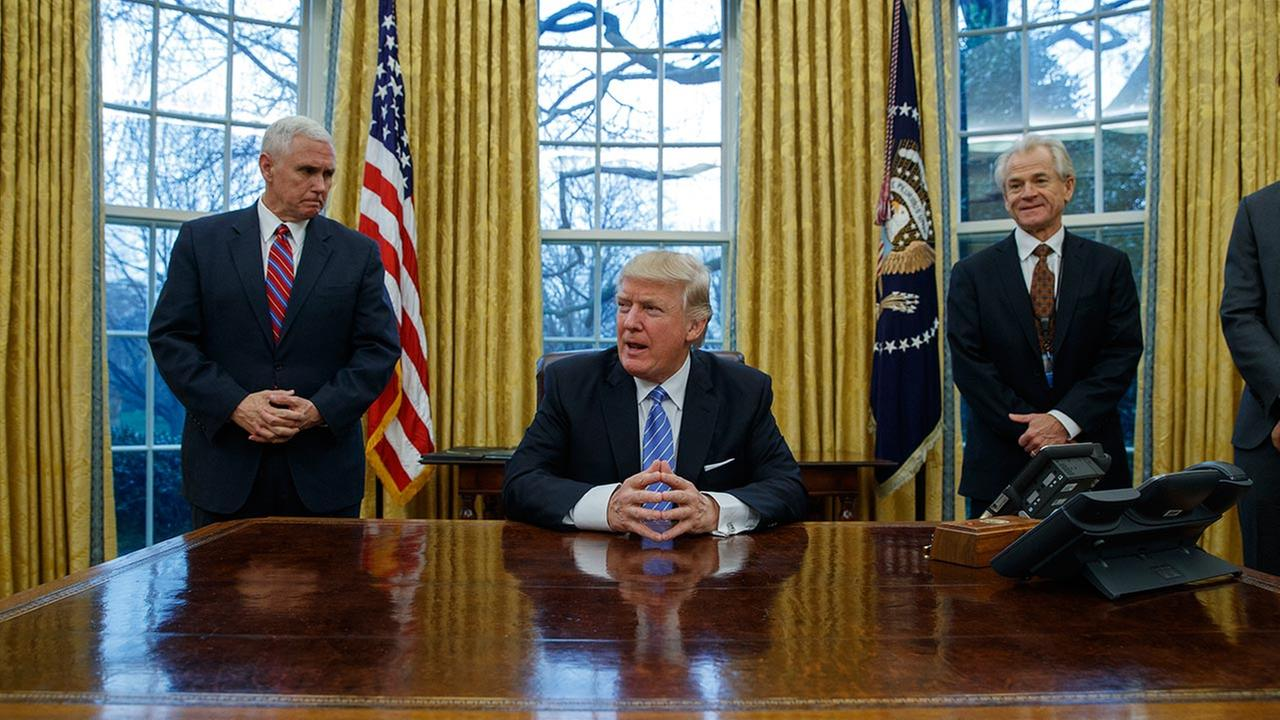 Vice President Mike Pence, left, and National Trade Council adviser Peter Navarro, right, wait for President Donald Trump to sign three executive orders, Monday, Jan. 23, 2017