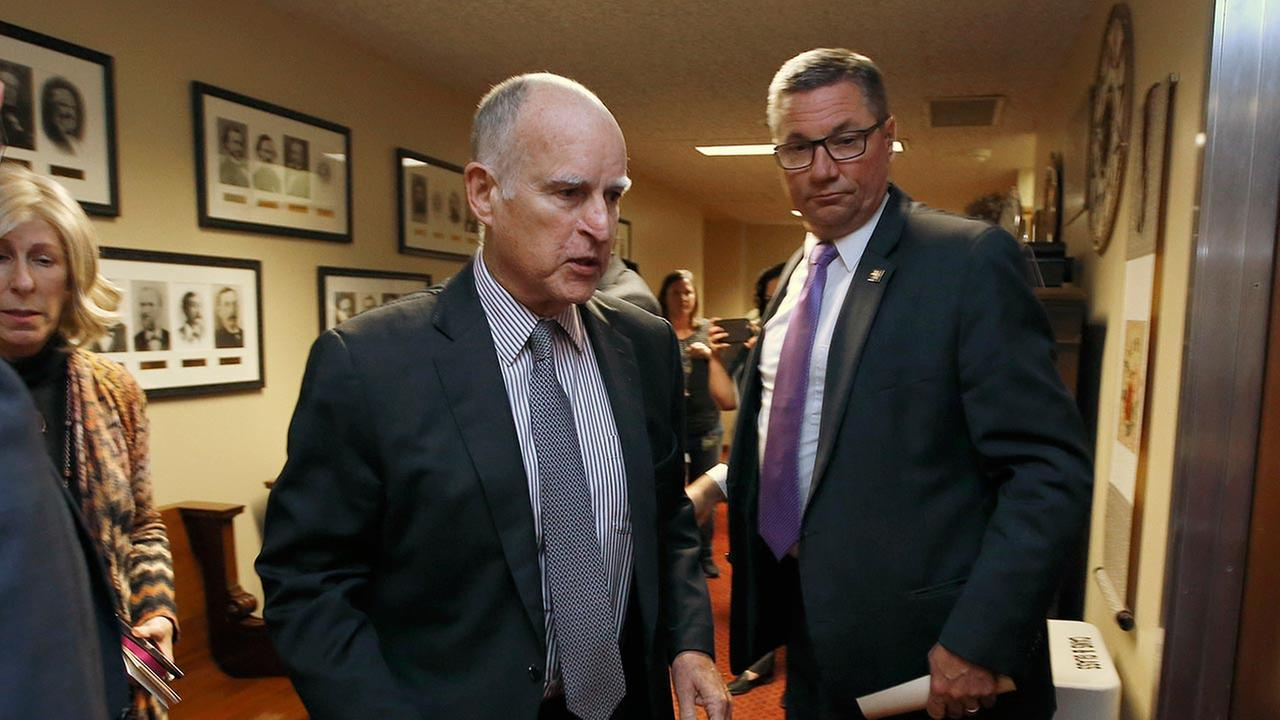 Gov. Jerry Brown walks into a meeting of the Senate Democratic Caucus to urge them to approve a transportation plan