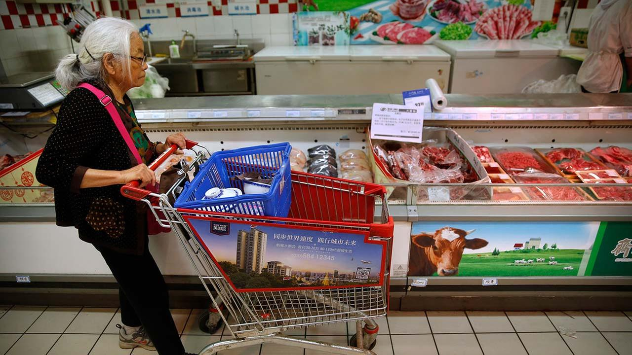 A woman pushes her shopping cart past a display of domestically produced Chinese beef at a supermarket in Beijing, Friday, May 12, 2017