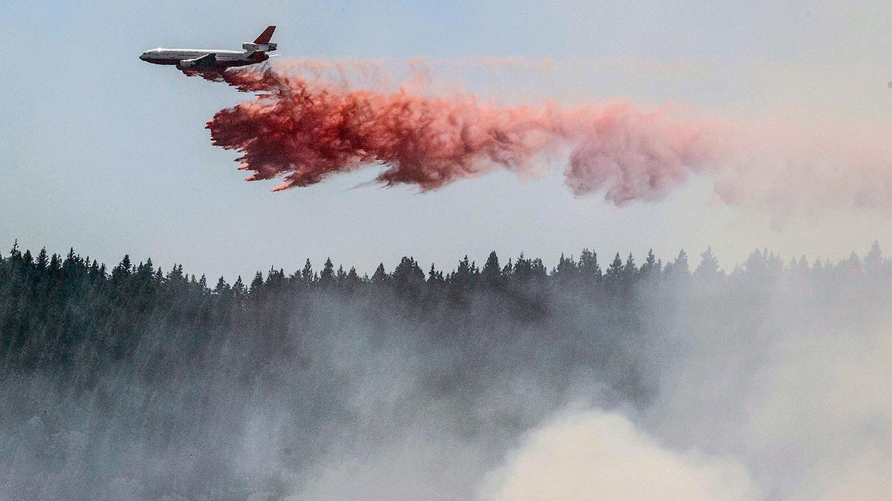 plane drops fire retardant as firefighters battle a blaze in El Portal, Calif., near Yosemite National Park on Tuesday, July 29, 2014