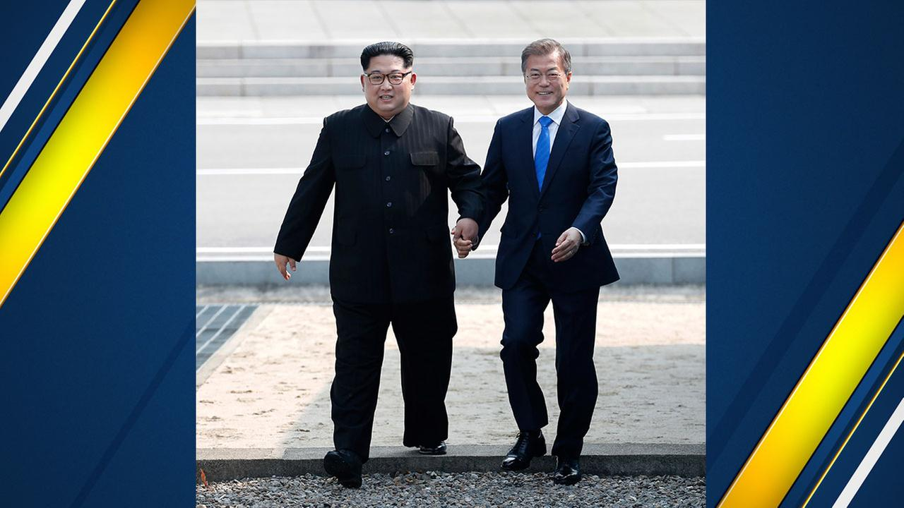 South Korean President Moon Jae-in gives a hand to North Korean leader Kim Jong Un as he crosses over the military demarcation line and into South Korea in the Demilitarized Zone.