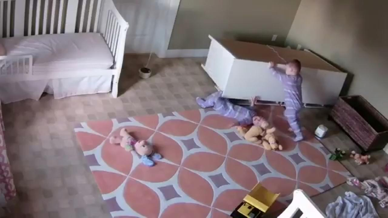 Twin boy pulls fallen dresser off his brother