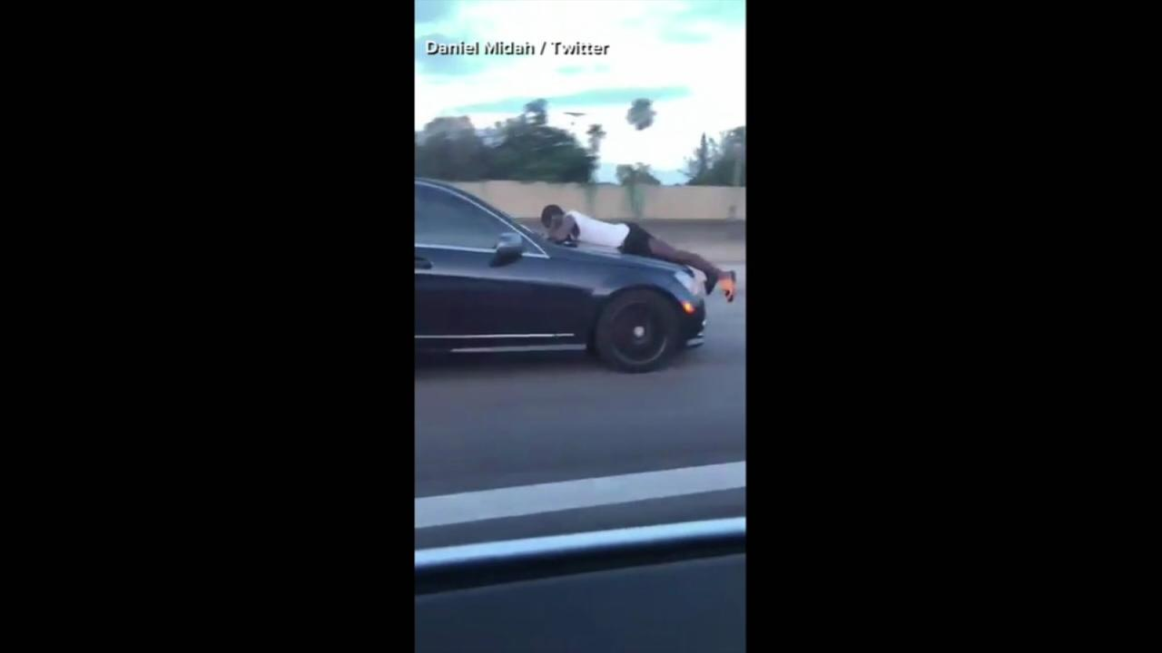Video shows man laying on hood of car as it travels down I-95