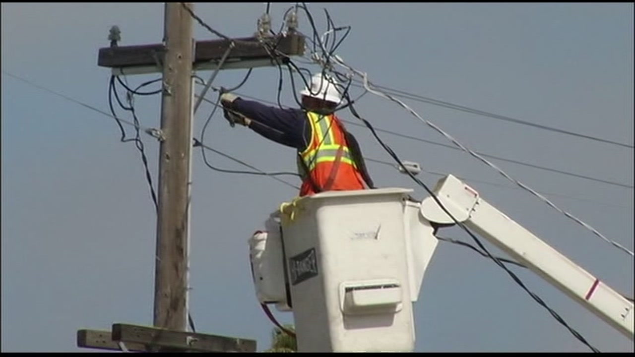 A PG&E worker adjusts lines on a power pole in this undated file photo.