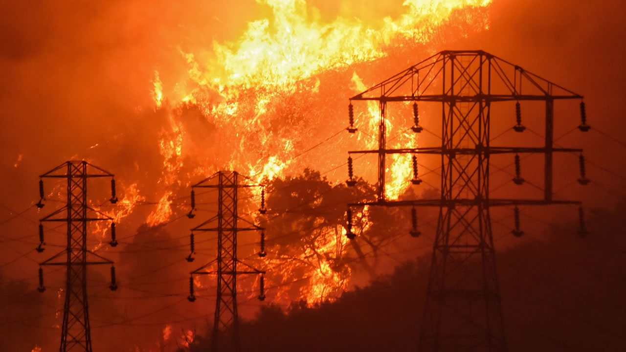 In this Dec. 16, 2017, file photo provided by the Santa Barbara Co. Fire Department, flames burn near power lines in Sycamore Canyon near West Mountain Drive in Montecito, Calif.