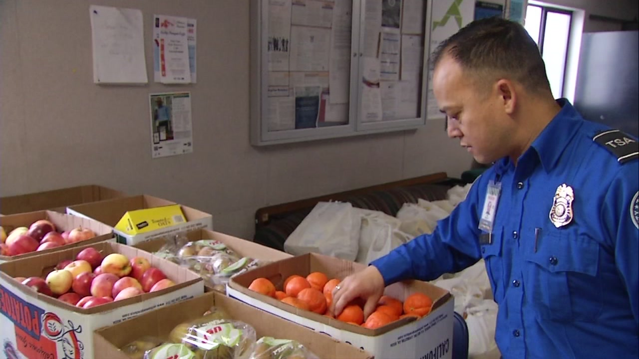 A TSA worker is seen grabbing fruit brought by a food bank at Oakland International Airport in Oakland, Calif. on Friday, Jan. 18, 2019.