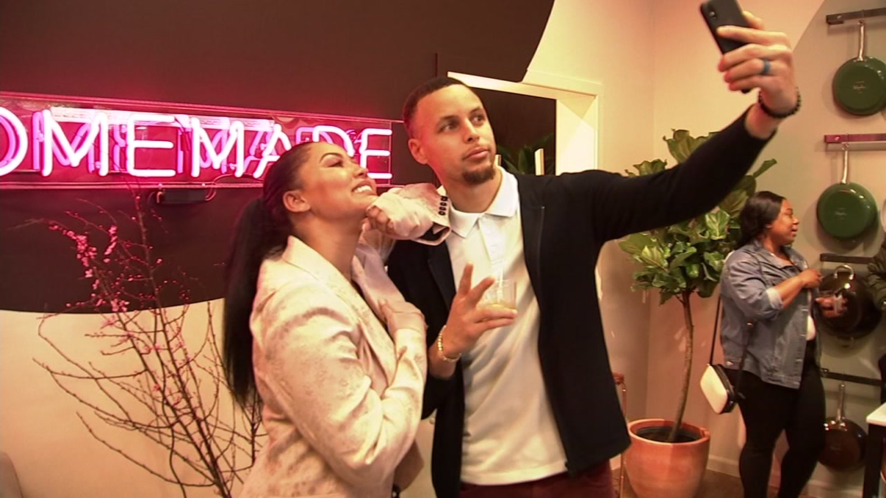 Ayesha and Stephen Curry pose for a picture inside Ayeshas pop-up shop in Oakland. Feb. 1, 2019