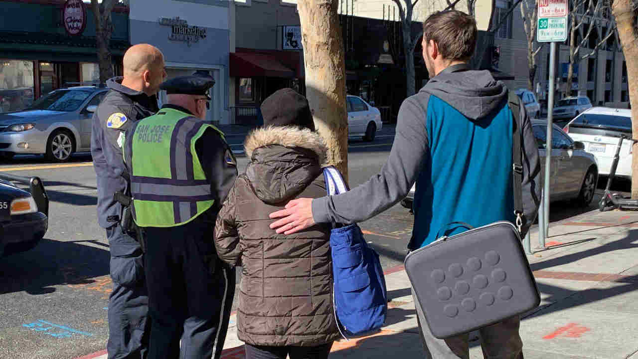 A Good Samaritan is seen next to a woman who had just been robbed in San Jose, Calif. on Tuesday, Feb. 4, 2019.