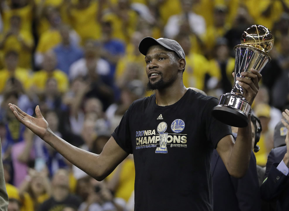 Warriors forward Kevin Durant gestures as he holds the Bill Russell NBA Finals Most Valuable Player Award after Game 5 of basketballs NBA Finals in Oakland, Calif., Monday, June 12, 2017. (AP Photo/Marcio Jose Sanchez)