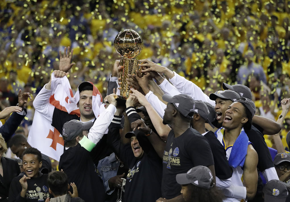 Warriors players, coaches and owners hold up the Larry OBrien NBA Championship Trophy after Game 5 of the NBA Finals in Oakland, Calif., Monday, June 12, 2017. (AP Photo/Marcio Jose Sanchez)