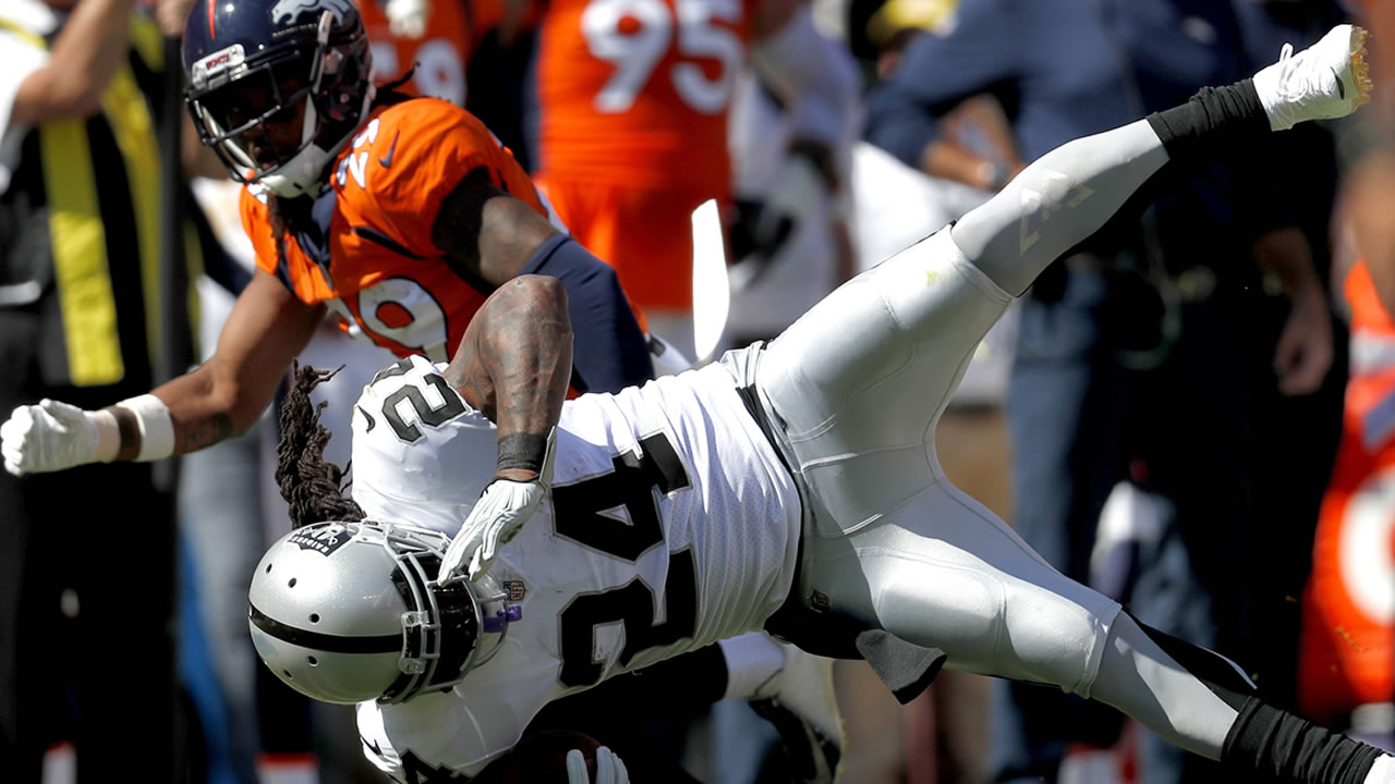 Oakland Raiders RB Marshawn Lynch is hit by Denver Broncos defensive back Bradley Roby during an NFL football game, Sunday, Sept. 16, 2018, in Denver.