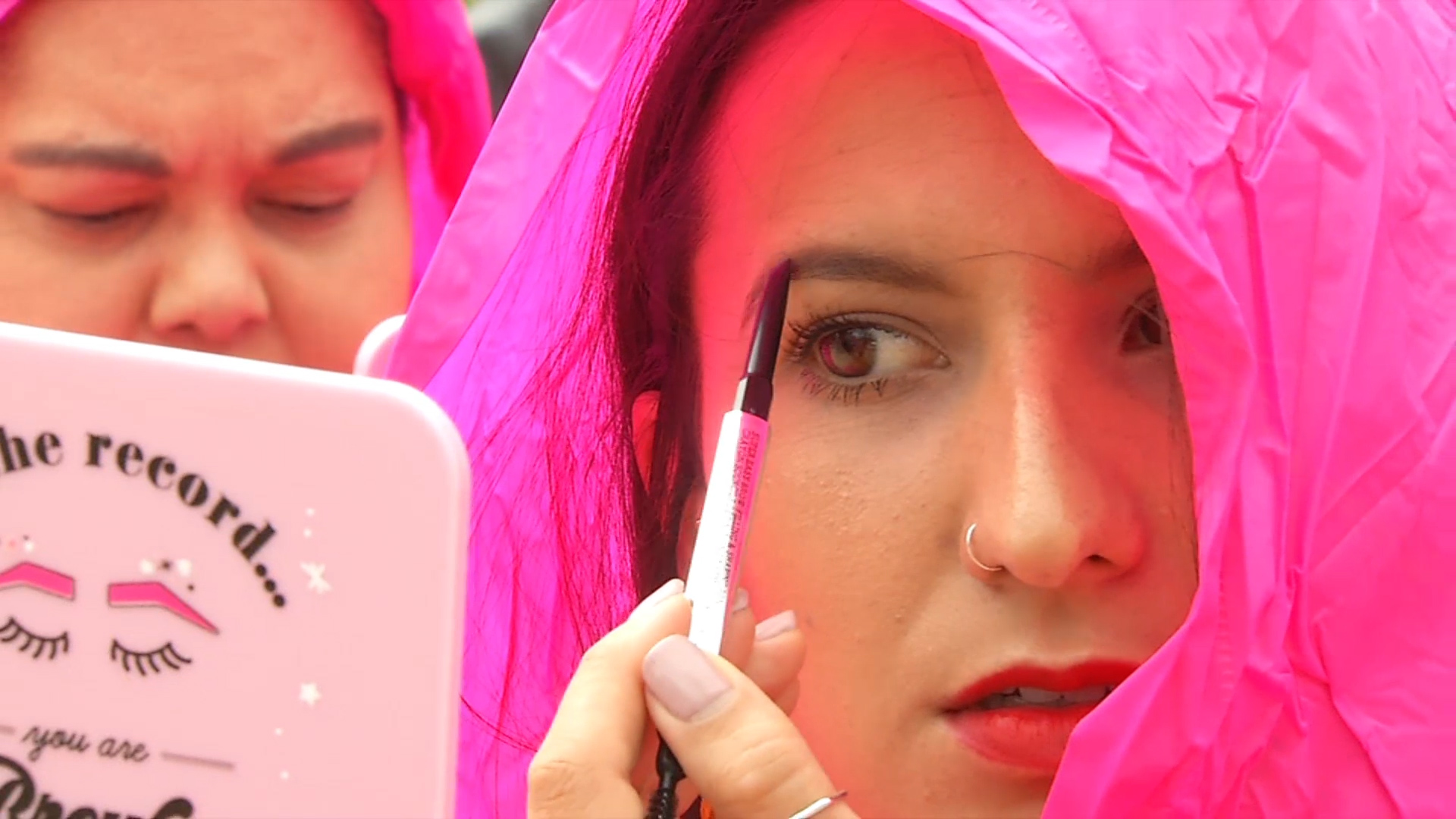 A woman fills her eyebrows with a crowd in order to break a world record in San Francisco on Sept. 28, 2018.