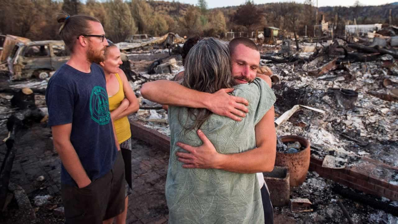 Charlie Liethen, right, embraces Sharon Dawson, who lost her home in a wildfire, in Middletown, Calif., Monday, Sept. 21, 2015.