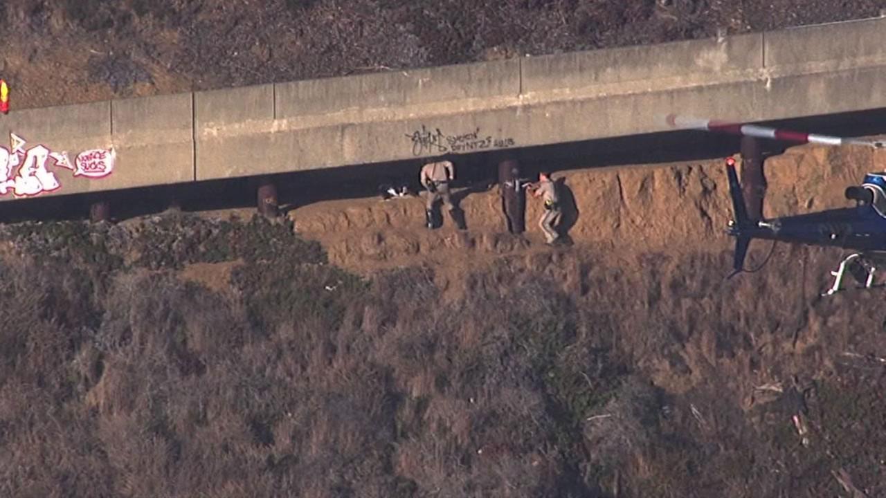 California Highway Patrol officers detain a man hiding underneath the roadway on Treasure Island, Sept. 28, 2015.