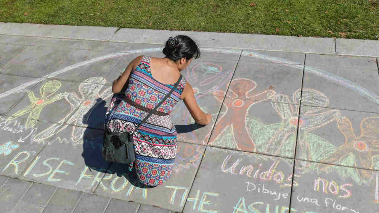 Elizabeth Jimenez Montelongo is seen working on a chalk mural on a sidewalk in Santa Rosa, Calif. on Tuesday, Oct. 9, 2018.
