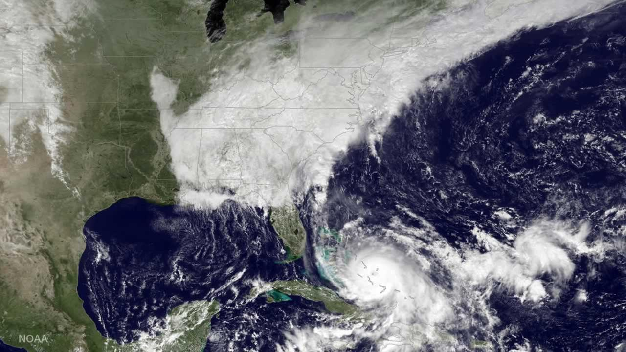 This satellite image taken Fri, Oct. 2, 2015 at 12:45 p.m. EDT, shows Hurricane Joaquin, bottom center, pounding the Bahamas and a deepening low pressure system on the East Coast.