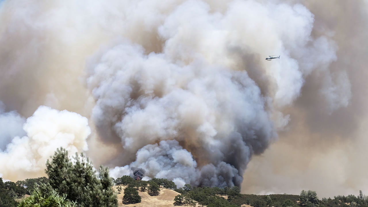 A chopper flies over wildfire blames in Sonoma County, Calif.