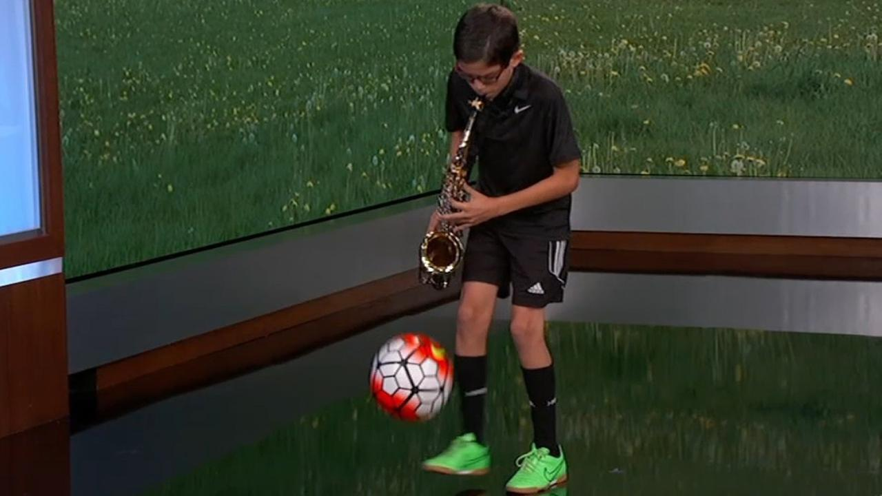 Kid kicks soccer ball while playing saxophone on Jimmy Kimmel Live! Tuesday, October 6, 2015.