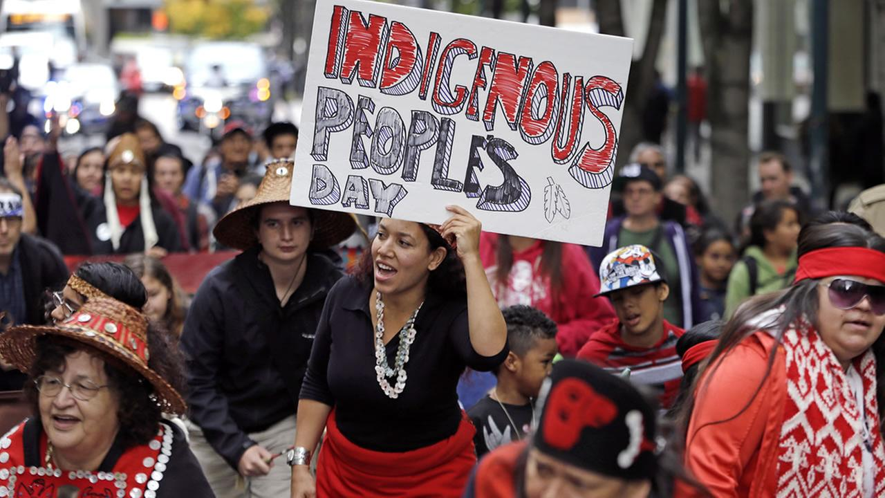 Miriam Zmiewski-Angelova, center, holds a sign for Indigenous Peoples Day during a demonstration and march, Monday, Oct. 12, 2015, in Seattle.