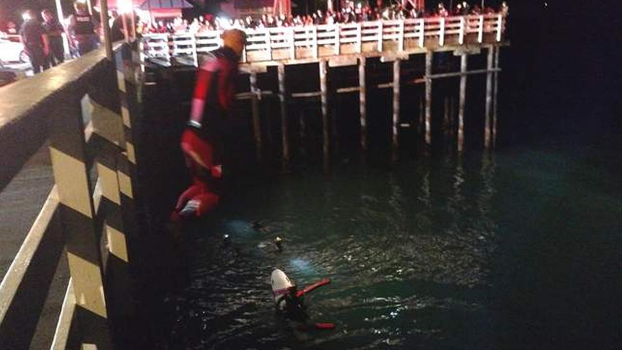 Santa Cruz firefighters rescue two people after a car drove off Municipal Wharf in Santa Cruz, Calif., on Saturday, October 17, 2015.
