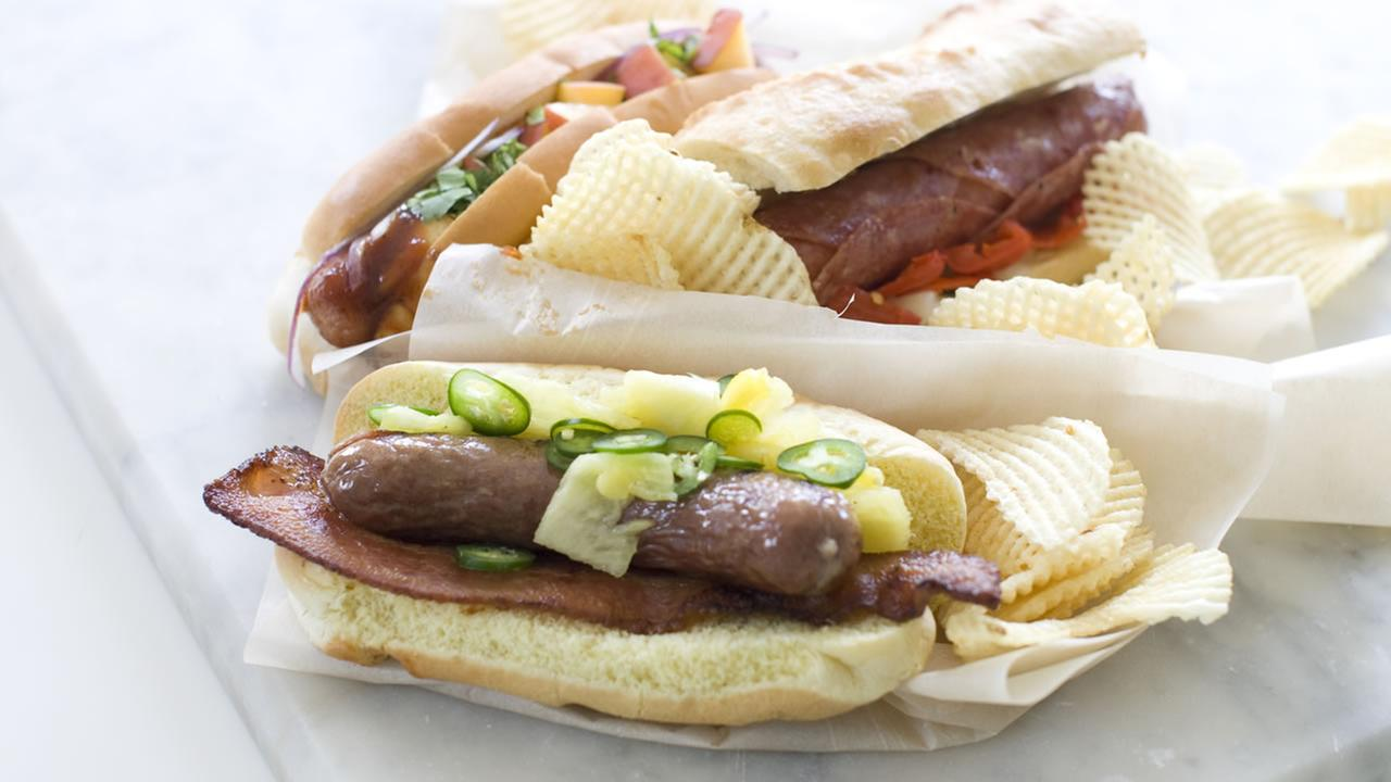 This June 29, 2013 photo shows, from top left, the sweet peach, Italian and Hawaiian hot dogs in Concord, N.H. (AP Photo/Matthew Mead)