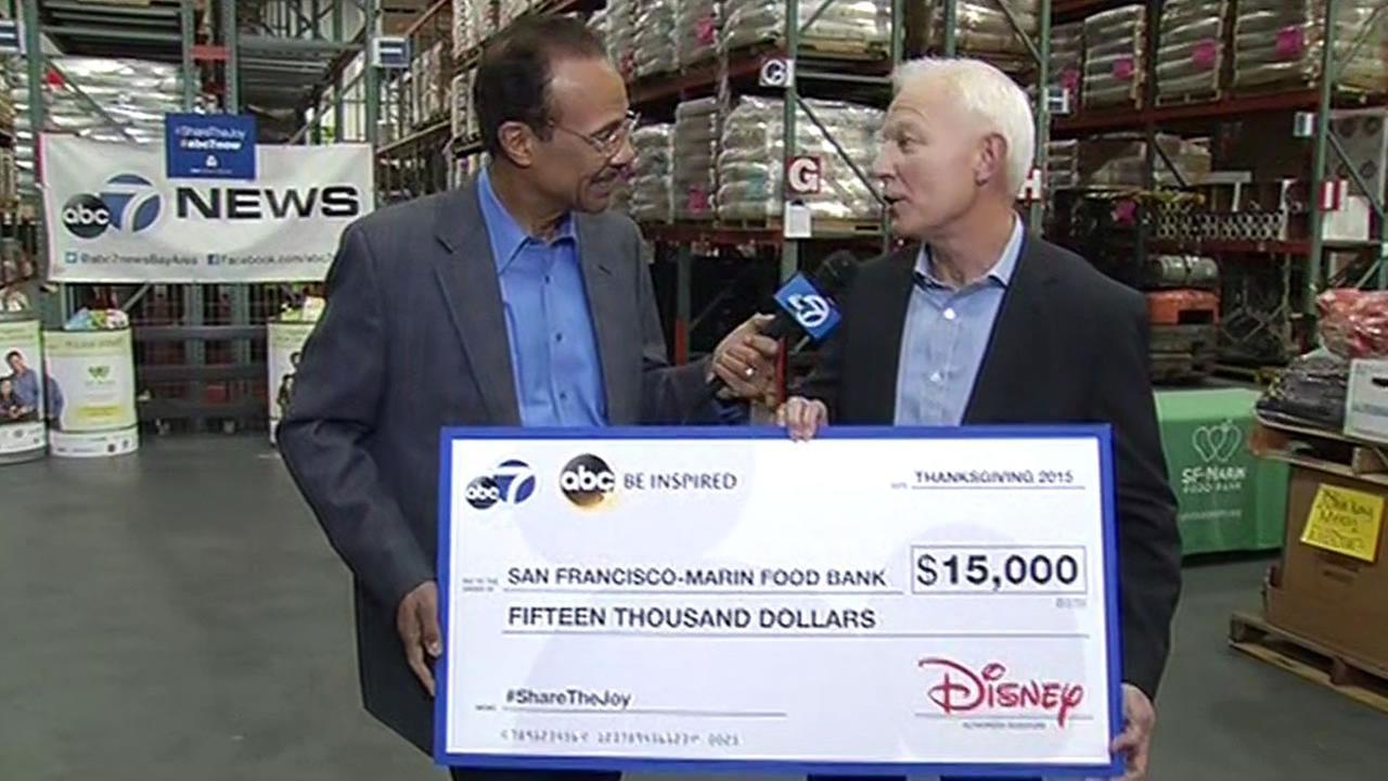 Spencer Christian presents a $15,000 check to SF-Marin Food Bank executive director Paul Ash in San Francisco on Monday, November 9, 2015.