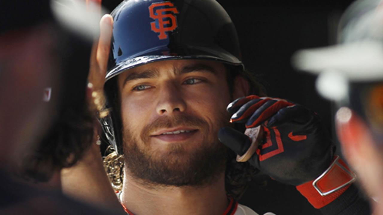 San Francisco Giants Brandon Crawford smiles in the dugout after hitting a home run against the Rockies during the fourth inning of a baseball game, Saturday, Oct. 3, 2015.