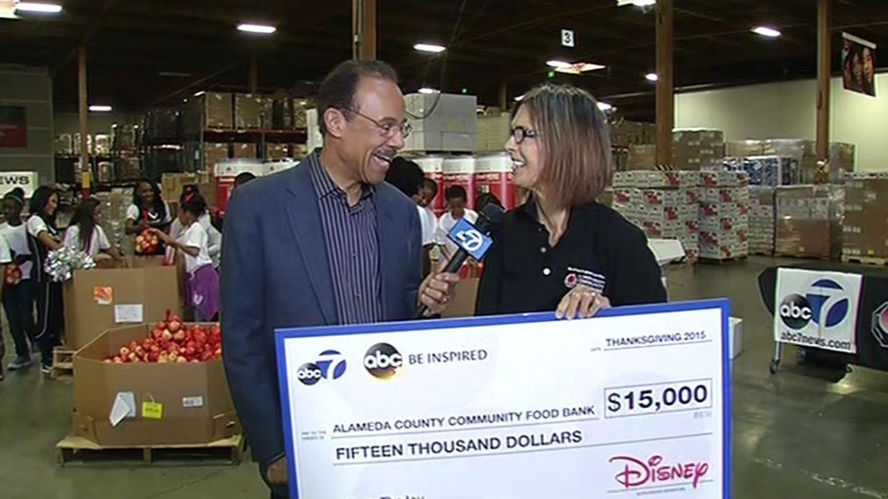 Spencer Christian presents a check for $15,000 to Alameda County Community Food Bank Executive Director Suzan Bateson in Oakland, Calif. on Wednesday, November 11, 2015.
