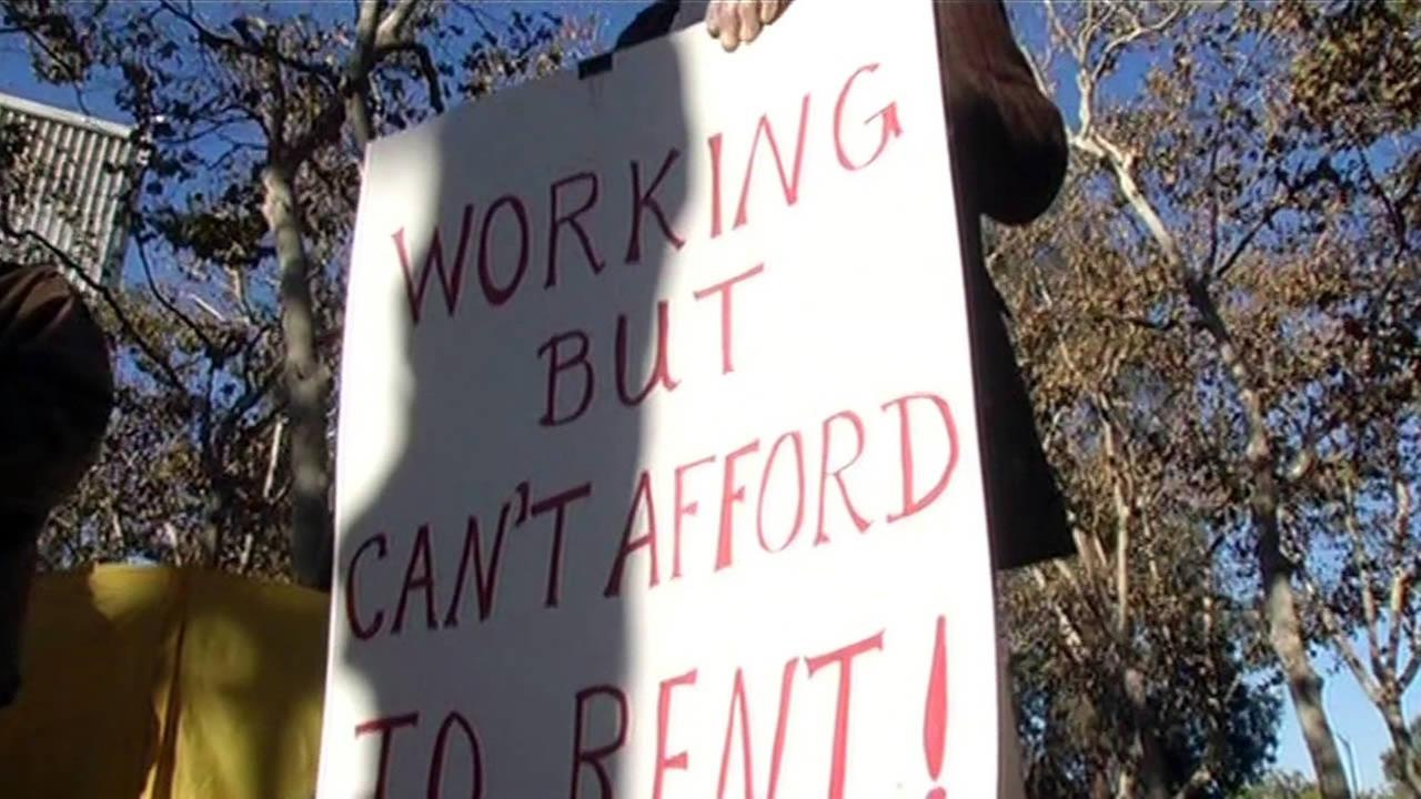 A demonstrator holds up a sign at a protest over the lack of affordable housing in San Jose, Calif. on Thursday, November 12, 2015.