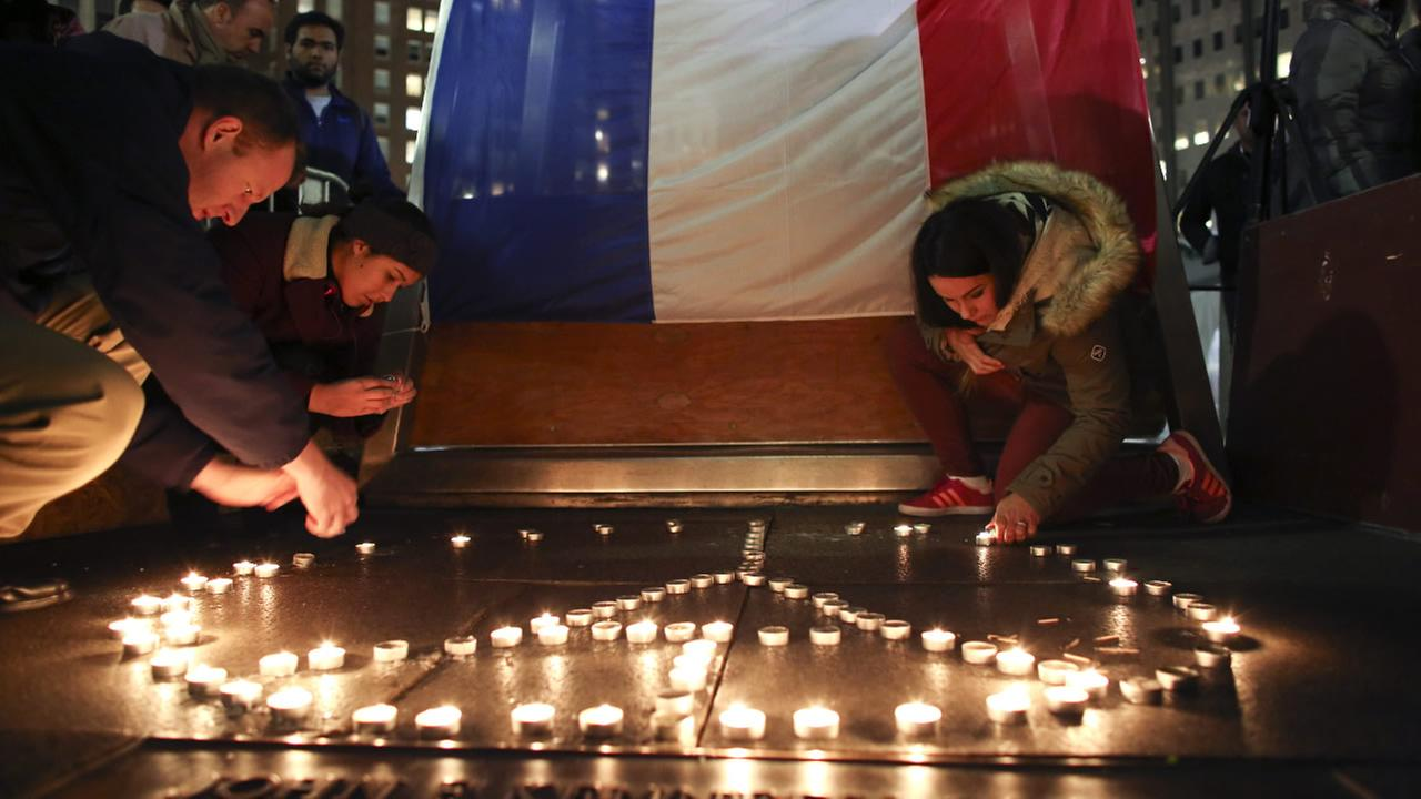 Stephane Fosik, Cedrine Plongeur and Cloe Tinchant light candles in LOVE Park, Saturday, Nov. 14, 2015, during a vigil to remember the victims of the Paris attacks.