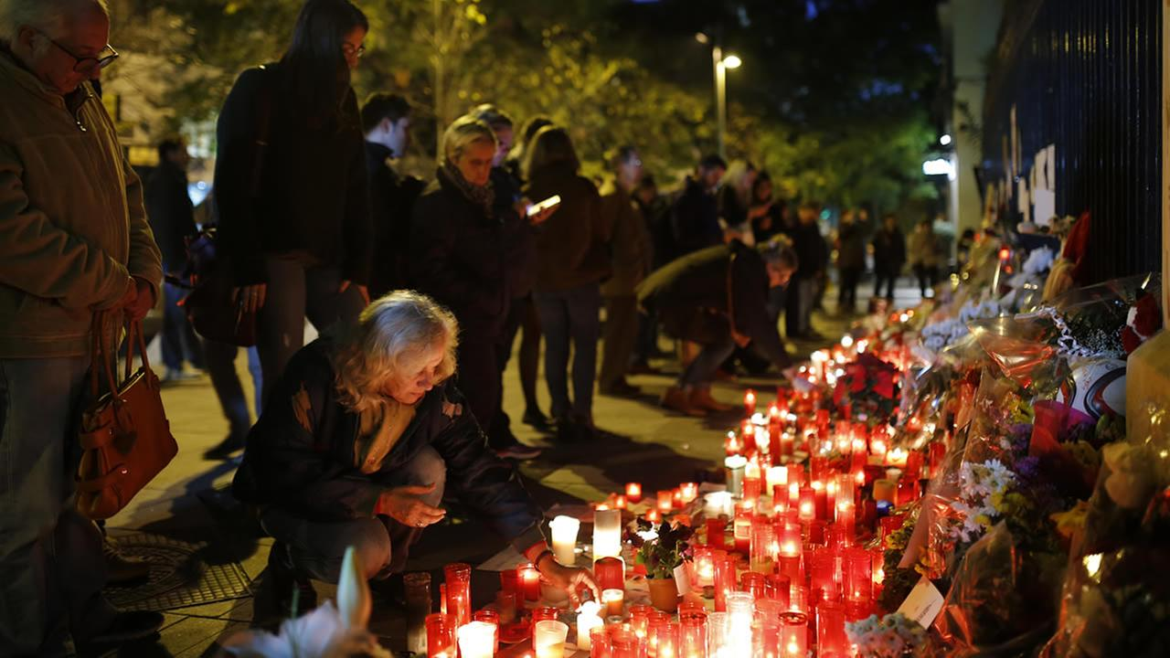 People place candles and flowers outside the French embassy in Madrid, Monday, Nov. 16, 2015.(AP Photo/Francisco Seco)