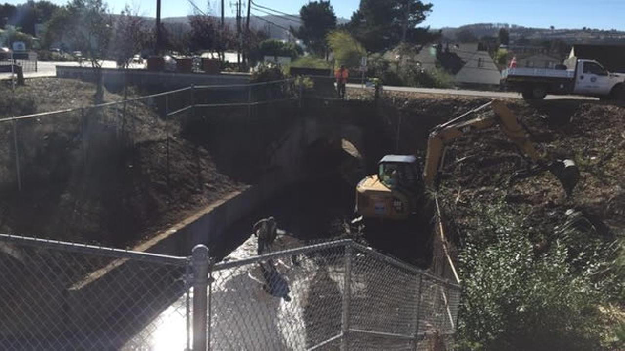 In this image, South San Francisco officials clear debris from the basin east of Centennial Trail to prepare for El Nino.