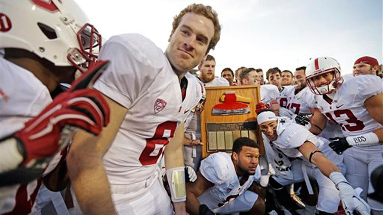 Stanford players including quarterback Kevin Hogan (8) celebrate with the Stanford Axe after defeating California 38-17 after an NCAA college football game Saturday, Nov. 22, 2014.