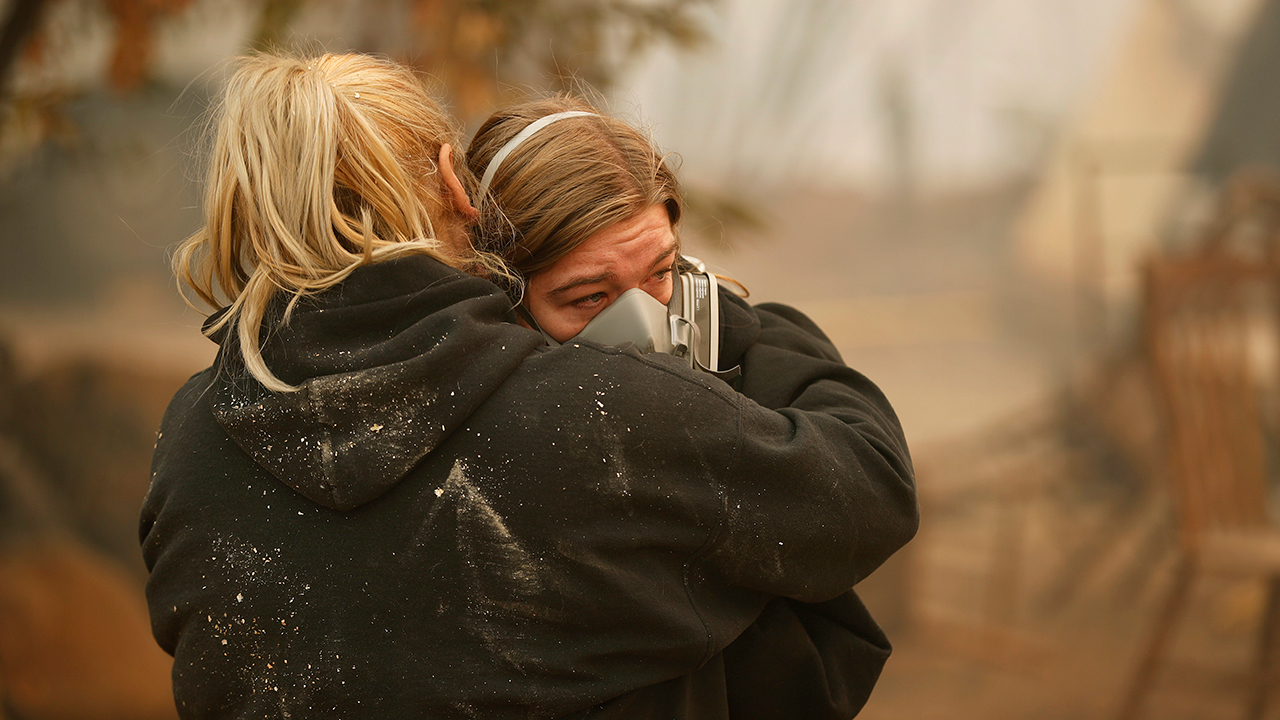 Krystin Harvey, left, comforts her daughter Araya Cipollini at the remains of their home burned in the Camp Fire, Saturday, Nov. 10, 2018, in Paradise, Calif.