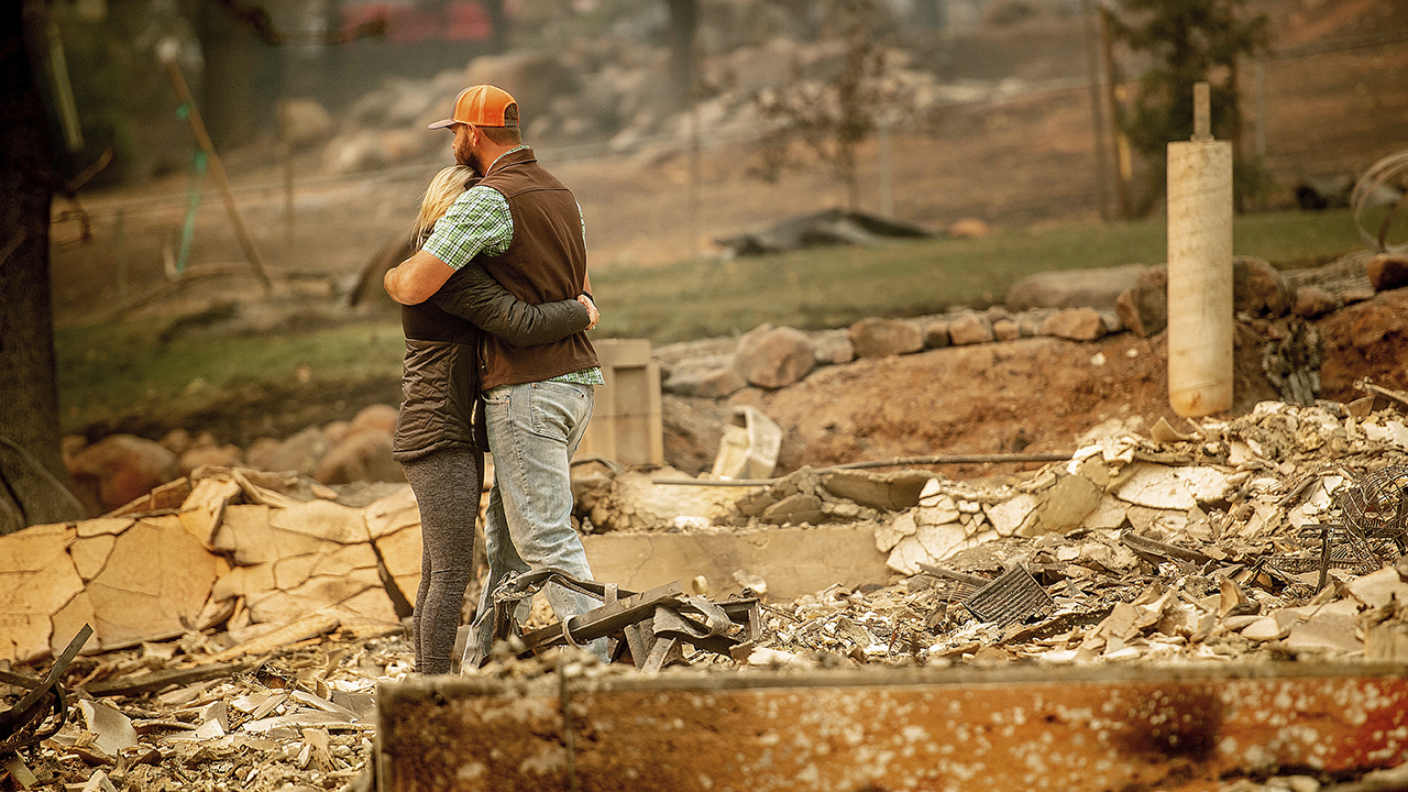 Chris and Nancy Brown embrace while searching through the remains of their home, leveled by the Camp Fire, in Paradise, Calif., on Monday, Nov. 12, 2018.