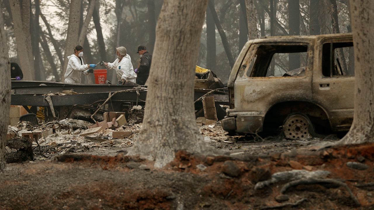 Investigators use a bucket to help recover human remains at a home burned in the Camp fire, Thursday, Nov. 15, 2018, in Magalia, Calif.