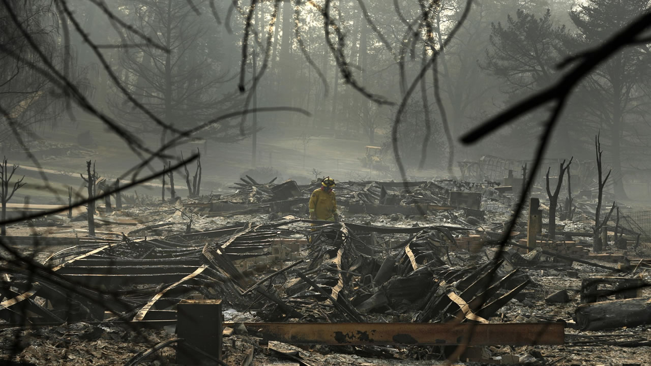 This image taken on Friday, Nov. 16, 2018 shows a firefighter searching through the Camp Fire rubble in Paradise, Calif.